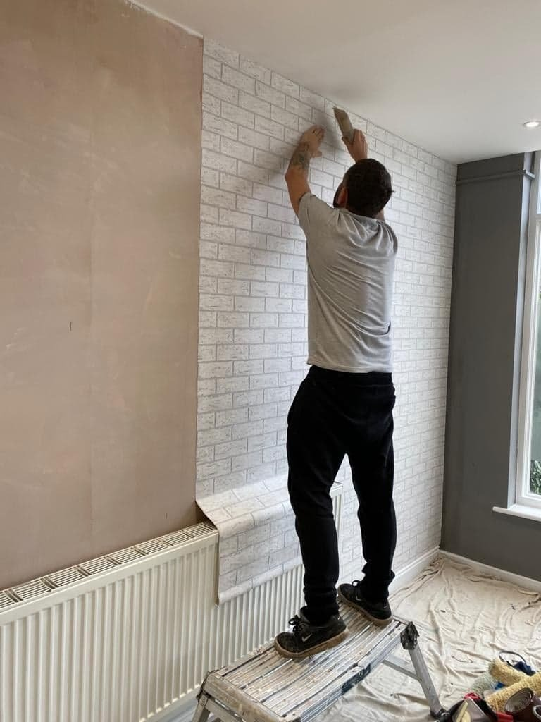Decorator applying wallpaper to a wall