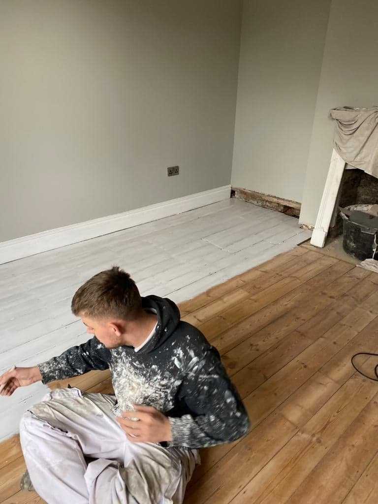 Decorator applying white flortred paint